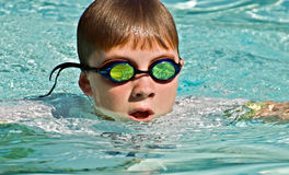 Close up of Boy Swimming. Close up of a preteen boy swimming. The waves and splashes in the pool are reflected in the goggles stock image