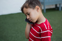 Close up of boy talking on mobile phone while standing on field Stock Photos