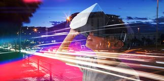 Composite image of close-up of boy wearing vr headset. Close-up of boy wearing VR headset against light trails on city street Stock Photos