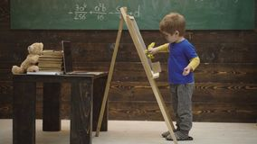 Close-up of a boy which writes with chalk on a board. Small artist paints on a wooden background. Concept of fine art stock video footage