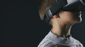 Close-up boy 10 years old using a virtual reality helmet. Child getting experience in using VR 360. Shot of a boy getting experience in using VR-headset stock footage