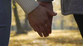 Close-up of boyfriend and girlfriend clasping each other hands in slow-motion
