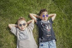 Close up of boys, brothers lying in the park on green grass. View from above. stock images