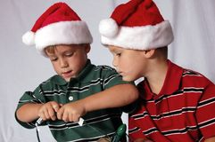 Close-Up Boys Playing with Lights. Twin boys playing with Christmas lights wearing Santa Hats Royalty Free Stock Photography