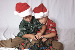 Close-Up Boys Playing with Lights. Twin boys playing with Christmas lights wearing Santa Hats Royalty Free Stock Images