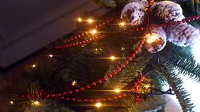 Close-up of branch of Christmas tree with garland. Frame. Branches of Christmas tree are decorated with garland, beads. And snow cones on background of simple stock video