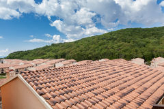 Close up of brand new red rooftop against blue cloudy sky and green forest Stock Photography
