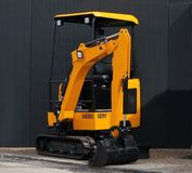 Close up of yellow mini excavator on black wall background royalty free stock photos