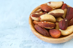 Close up of brasil nuts in a wooden plate. On white background stock photos