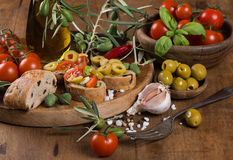 Close up of  bread with green olives and olive oil on a wooden s Stock Photos
