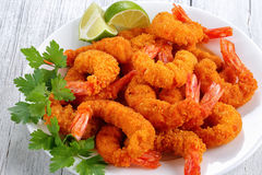 Close-up of breaded Fried Shrimp tails. Close-up of light and crispy crunchy bread crumbs coating Fried Shrimps with lime wedges and parsley on white plate on royalty free stock photography