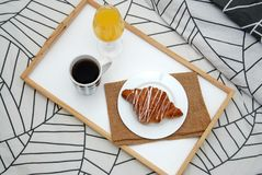 close up Breakfast in Bed. Coffee and Croissants White Chocolate Food. Cup of Coffe or Tea. Orange juice. Stock Photo