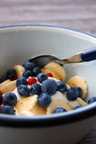 A close-up of a breakfast bowl of fresh fruits and Greek yoghurt on a rustic wooden table. Ready to be eaten royalty free stock images