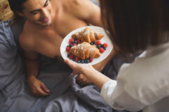 Close up of breakfast in woman hands. Close up of a women holding breakfast in front of a man Stock Photo