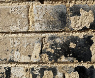 Rugged Brick Wall - Close Up. Close up of a brick wall covered with rough texture, which seems to be old plaster and tar remains Royalty Free Stock Photos