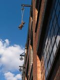 Close-up of brick wall warehouse building exterior with pulleys against blue sky with white clouds. stock photo