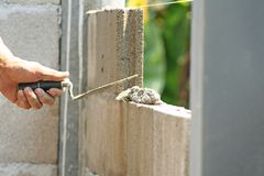Bricklayer worker installing cement blocks wall stock image