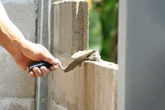 Bricklayer worker installing cement blocks wall royalty free stock image
