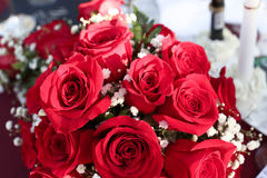 Close up of bridal bouquet of red roses on table. A bride`s bouquet of red roses and white baby`s breath flowers is lying on a table at a wedding reception Royalty Free Stock Photography