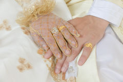 Close-up a bride and groom covers of each other's hands. With rings (Islamic religion Stock Image
