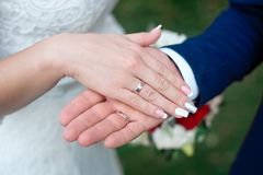 Close-up Bride and groom`s hands with wedding rings. Groom putting golden ring on finger. Love and marriage Stock Photography