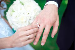Close-up Bride and groom`s hands with wedding rings. Groom putting golden ring on finger. Love and marriage Stock Photos