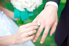 Close-up Bride and groom`s hands with wedding rings. Groom putting golden ring on finger. Love and marriage Royalty Free Stock Images