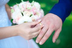Close-up Bride and groom`s hands with wedding rings. Groom putting golden ring on finger. Love and marriage Royalty Free Stock Photography