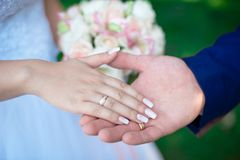 Close-up Bride and groom`s hands with wedding rings. Groom putting golden ring on finger. Love and marriage Stock Images