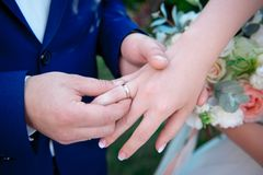 Close-up Bride and groom`s hands with wedding rings. Groom putting golden ring on finger. Love and marriage Stock Image