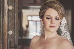 Bride portrait in front of rustic door. A close-up of a bride with long lace veil  in front of vintage bank vault door Stock Photography