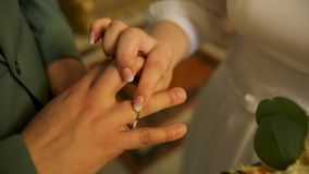 Close up Bride Put the Wedding Ring on Groom. Love and marriage. Wedding ceremony. Close up of groom putting golden ring stock footage