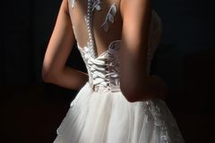 Close-up of a bride`s corset in a sun rays. royalty free stock image