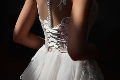 Close-up of a bride`s corset in a sun rays. stock photos