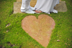 Close-up of bride`s and groom`s feet standing on green grass Royalty Free Stock Images