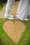 Close-up of bride`s and groom`s feet standing on green grass Royalty Free Stock Photography