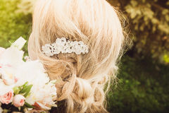 A close-up of the bride`s hairstyle holding the bouquet in her hands on the nature background. Stock Photography