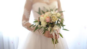 Close up of bride`s hands holding beautiful wedding bouquet of flowers of pink and white color. stock footage