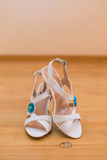 Close up of bride's shoes and gold rings Stock Image