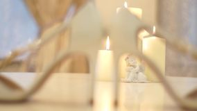 Close-up of a bride shoes on a table with burning candles. Close-up of a bride shoes on a table with candles and a figure of an angel stock video footage