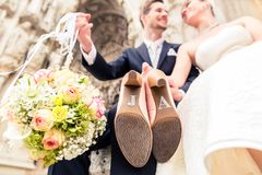 Close-up of newly wed couple. Close-up of bridegroom holding bouquet ball and bride showing wedding shoe sole royalty free stock photography