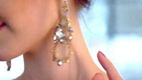 A close-up on the brides face gently touches beautiful designer earrings. Macro stock footage