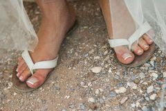 A close up of brides legs in flip flops on a beach with manicured nails stock photo