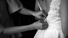 Dressing bride for wedding. Close up bridesmaid helping the bride to dress before the ceremony Royalty Free Stock Photography