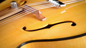 Close up of bridge, strings, efe and wood of classic jazz electric guitar gyrating at black background. Classic Electric Guitar Jazz Rotating in Horizontal stock footage