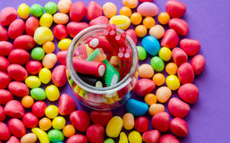 Close-up of bright candies and jar with liquorice. Close-up of colorful candies and jar with liquorice.From above Stock Photo
