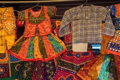 Colorful children`s clothes in Indian market. Close up bright clothing for kids on hangers for sale on Indian market Royalty Free Stock Photography