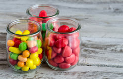 Close-up of bright colorful candies in bowls. Close-up of red,yellow and pink candies in glass jars on wooden table Stock Photos