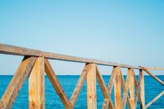 Close-up of bright orange brown wooden fence and a blue sea at t Royalty Free Stock Image
