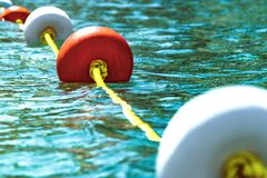 Close-up bright red and white coloers buoys on the surface of the water. Depth marks. Safety on sea.  stock images